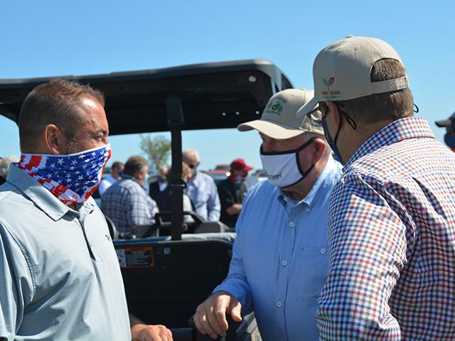 Kevin Ross, an Iowa farmer and president of the National Corn Growers Association, left, talks with Agriculture Secretary Sonny Perdue at a conservation event on a farm near Radcliffe, Iowa, on Thursday. Perdue declared an agricultural disaster for 18 counties hit hard by a windstorm in mid-August. (DTN photo by Chris Clayton)