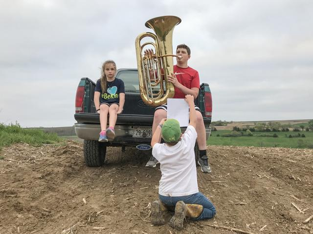 Kyle Quinn, 15, plays his tuba from a high spot on the Quinn farm in order to get a strong enough mobile phone signal to send his performance to his band teacher. Brother Burke, 10, holds the music and sister Ella, 8, listens. (DTN photo by Russ Quinn.)