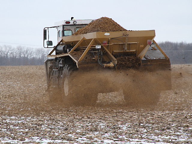A manure spreader passes over a field. (DTN file photo)
