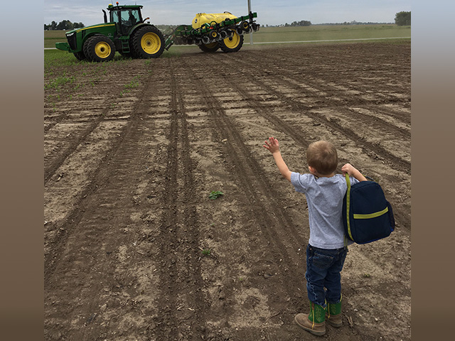 William Pistorius flags down his father, Pete, to take a healthy and therapeutic lunch break during spring planting near Blue Mound, Illinois. (Photo Courtesy of Pistorius Farms)