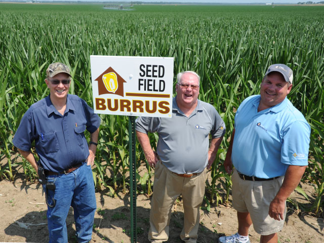 This is how Tom Burrus (center) approached life -- gung ho and smiling -- even in the face of drought, which was evident in their seed fields in 2012 when this photo was taken. His brother Todd, and son-in-law, Tim Greene are standing alongside. (DTN photo by Pam Smith)