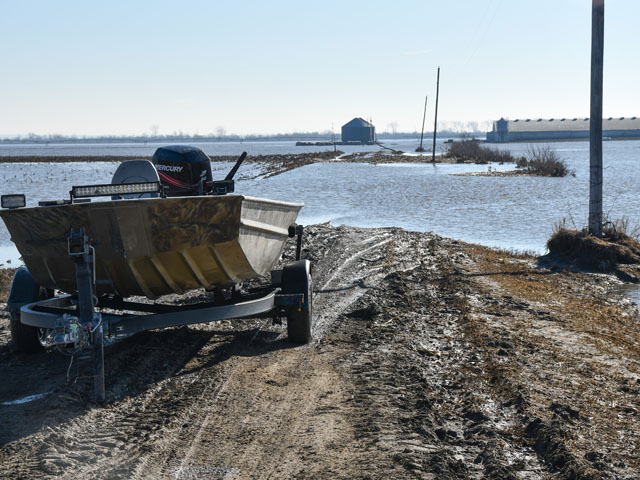 A motorboat sits ready to reach a hog building surrounded by Missouri River flood waters east of Herman, Nebraska. The hog building was not flooded, as it was built up higher, but the lane leading to the building was underwater. (DTN photo by Russ Quinn)
