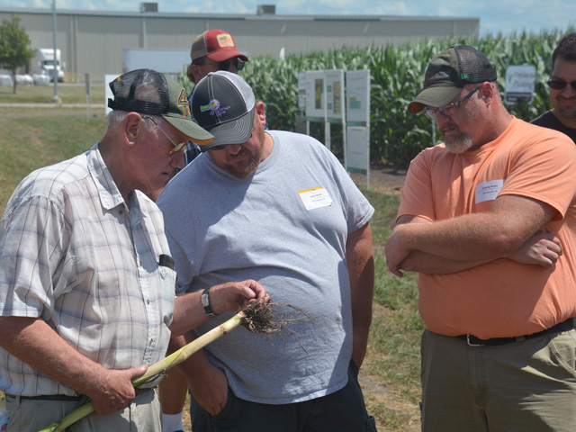 Charles Jacobi (left), Josh Jacobi (center) and Jeremy Amos check out corn root develop this summer at a research plot during a Precision Planting field day in Pontiac, Illinois. (DTN/Progressive Farmer photo by Matthew Wilde)