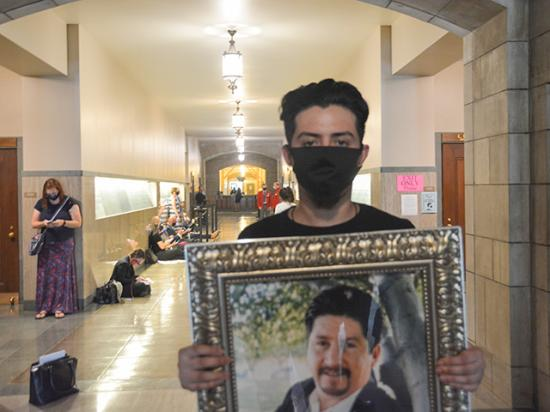 At the Nebraska Capitol on Thursday, Christian Munoz holds a portrait of his father, Rogelio Munoz Calderon, who died of COVID-19 in May at the age of 52. (DTN photo by Chris Clayton)