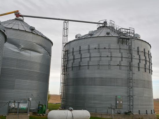 Wade Wilson, who farms near Dysart, Iowa, had wind rings installed on the bin on the right when it was built, which helped it survive the recent derecho. The bin on the left didn't have wind rings or other options to help it withstand prolonged, violent winds. (DTN/Progressive Farmer photo by Matthew Wilde)