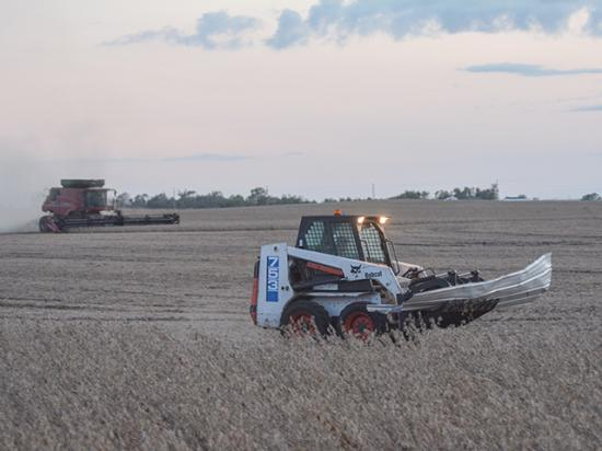 Mike Ihle combined a field of lodged soybeans just east of Madrid, Iowa, on Sept. 23 as one of his employees picked up debris with a grapple bucket on a Bobcat. The August derecho littered the field with tin, wood with nails in it and other material causing periodic breakdowns. (DTN photo by Matthew Wilde)