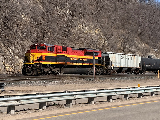 A Kansas City Southern engine behind a buffer car at the end of a tank car train pulled by the Canadian Pacific along the Mississippi River bluffs in downtown St. Paul, Minnesota, late March. (DTN photo by Mary Kennedy)
