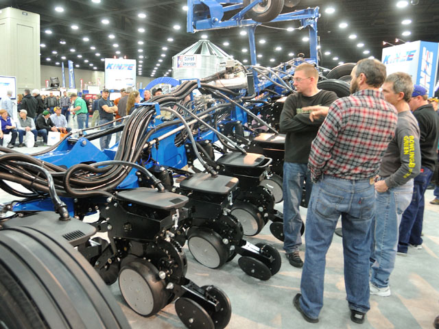 Farmers browse a planter at a farm machinery show. The new tax law will change the way farmers look at writing off major equipment purchases. (DTN file photo by Jim Patrico)