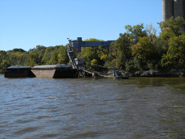 Barges waiting to be loaded with new crop sit in front of a river terminal in the Upper Mississippi River. River conditions heading south to the Gulf are still not ideal for the harvest rush of corn and especially soybeans to the Gulf. (DTN photo by Mary Kennedy)