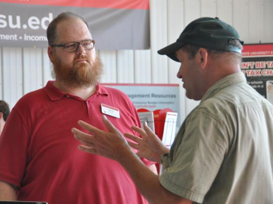 Ohio State climate researcher Aaron Wilson talks with an attendee at the Farm Science Review, where he is highlighting the need for local solutions to climate change. (DTN photo by Emily Unglesbee)