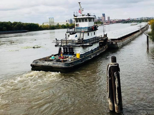 A tow pushes barges on the swollen Mississippi River near St. Paul, Minnesota. (Photo by Michelle Heck Webster)