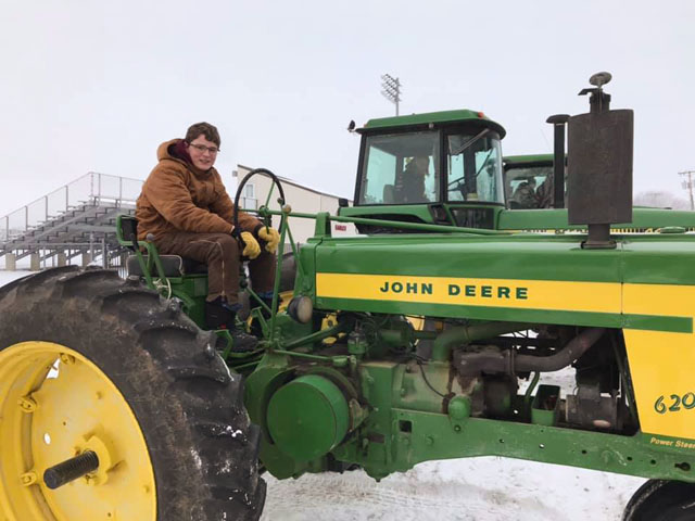 FFA students in Arlington, Nebraska, participated in a National FFA Week event to drive tractors to school on Feb. 19. Shown here is Kyle Quinn on his great grandfather's 620. FFA members who also drove tractors to school that day were Cassidy Arp, Blake Kracl and Kobe Wilkins. (Photo courtesy of Jill Hensley)