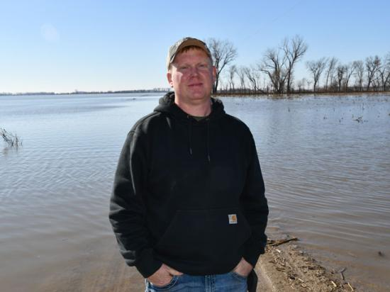 Tekamah, Nebraska, farmer Quentin Connealy stands near one of his flooded fields just west of the swollen Missouri River. The road behind him leads to his farm that he can't access. (DTN photo by Russ Quinn)