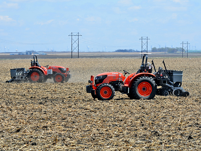 A Kubota tractor autonomously operated by Sabanto plants soybeans while another goes to the seed tender. (Progressive Farmer image by Matthew Wilde)