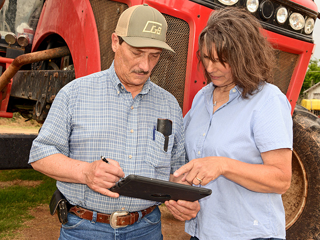 Karen Eifert Jones and husband, Rodney, consult field records before heading to the field to spray. (Progressive Farmer image by Larry Reichenberger)