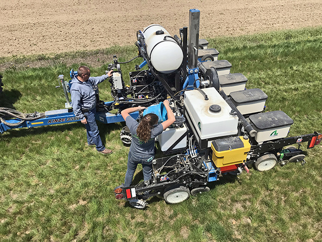 AgroLiquid employees Tim Duckert and Micalah Blohm work on and fill a planter at the company's North Central Research Station in St. Johns, Michigan. (Progressive Farmer image provided by AgroLiquid)