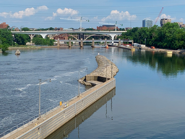 The new I-35W bridge can be seen downriver from St. Anthony Falls after the original bridge collapsed into the Mississippi River Aug. 1, 2007, killing 13 people and injuring 145. In 2005, the bridge was rated as structurally deficient and in possible need of replacement, according to the U.S. Department of Transportation National Bridge Inventory database. An inspection carried out on June 15, 2006, found problems of cracking and fatigue. On the right is the pool to the now-closed St. Anthony Lock and Dam. The Water Resources Reform and Development Act of 2014 prompted that closing, and while no reason was specified for the lock closure, it was surmised as an attempt to stop the spread of Asian carp upriver from the Falls. (DTN photo by Mary Kennedy)