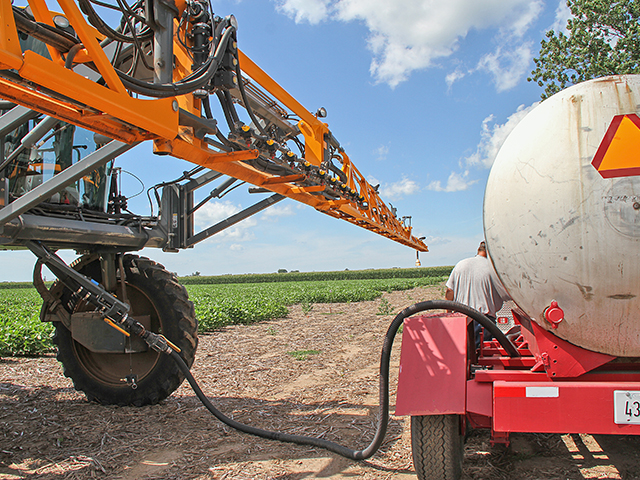 A sprayer is loaded with herbicides in central Illinois. Farmers and retailers are running into tight supplies and shipping delays for certain ag chemicals, particularly herbicides, this spring. (DTN photo by Pam Smith)