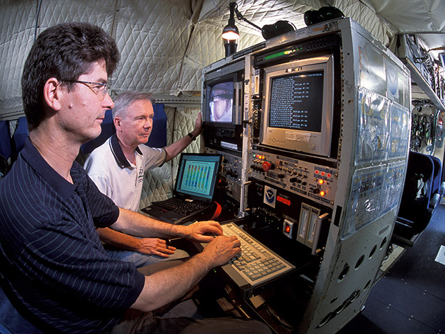 USDA-ARS hydrologist Tom Jackson, center, examines data from NASA's new soil moisture satellite while on board a NASA airplane. (Photo courtesy Stephen Ausmus, USDA-ARS)
