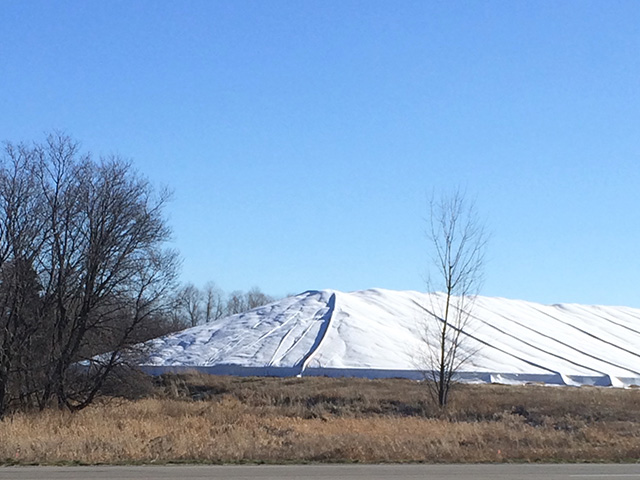 A ground pile of corn near Sartell, Minnesota, on March 27, 2016. This pile stretches out beyond the picture and is approximately 750,000 bushels. Like most piles around the Midwest that are still standing, it has been in the same spot since Harvest 2015. (DTN photo by Mary Kennedy)
