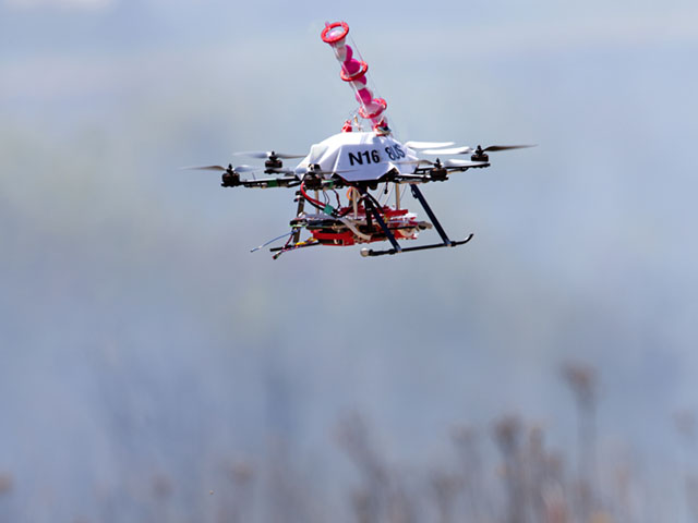 Engineers at the University of Nebraska-Lincoln have developed a drone able to light controlled prairie burns using balls dropped from the sky. The drone injects a liquid into the plastic spheres to start a delayed fiery process so the balls can fall to the ground before igniting. (Photo by Craig Chandler, University Communications, University of Nebraska-Lincoln)