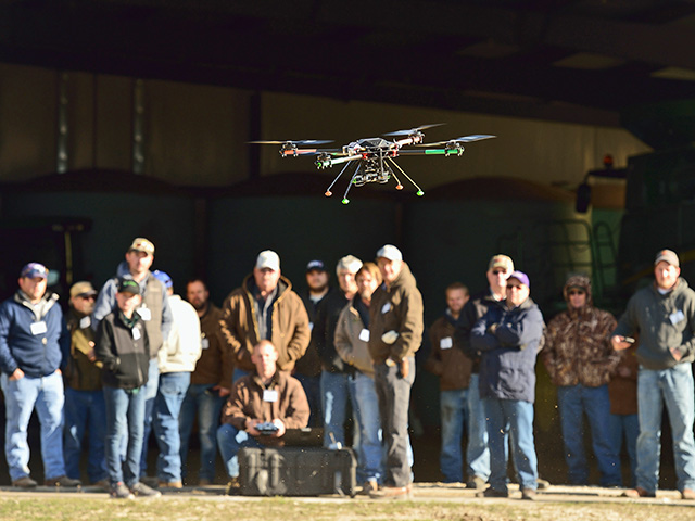 At a UAV workshop in Kansas, farmers and others watch a drone go through its paces. (Progressive Farmer photo by Jim Patrico)