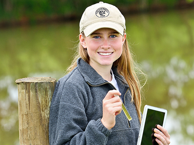 Using a test tube of water, high school senior Hannah Thomas checks the family cattle farm's water quality by color and tracks results with a tablet. (DTN/Progressive Farmer photo by Jim Patrico)
