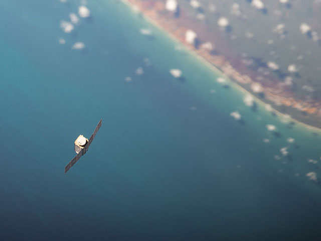 A tiny Dove satellite floats over the Earth after being deployed from the International Space Station. (Photo courtesy of NASA)