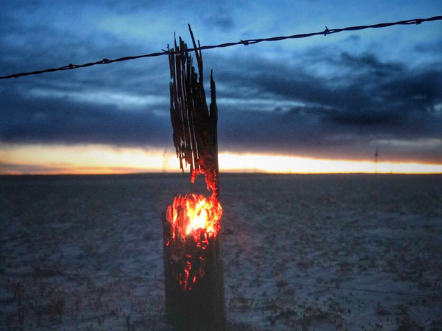 The charred remains of a wooden fencepost continue to burn after wildfires swept through northeastern Colorado on Tuesday. Wildfires across the entire High Plains region destroyed homes, farm buildings, fences, crops and livestock, and also resulted in the loss of human lives. (Photo courtesy of Ryan Kanode Haxtun, Colorado)