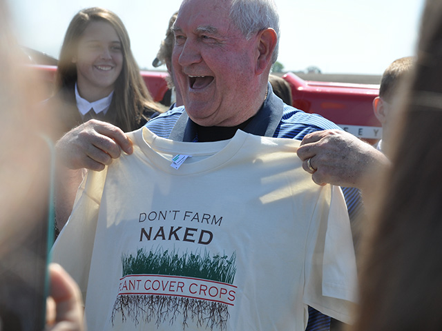 "U.S. Agriculture Secretary Sonny Perdue holds up a t-shirt from ""Practical Farmers of Iowa,"" touting cover crops in the state. Perdue got a good laugh out of it during his trip to a feedyard near Nevada, Iowa, on Friday. (Photo by Chris Clayton)"