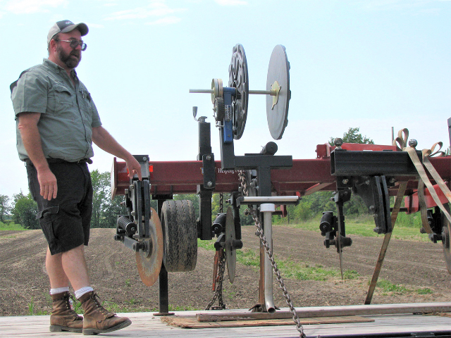 MU Extension agronomist Rusty Lee shows a modified conservation ripper used to bury drip tape for irrigating corn and soybean fields. (DTN/The Progressive Farmer photo by Linda Geist)