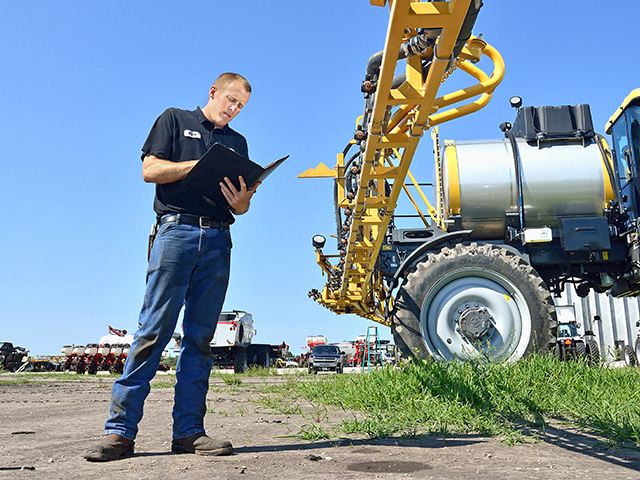 Kyle Eisenmann, a service technician for Butler Ag, in Fremont, Nebraska, does a 360-degree walk-around with a notebook to record issues. (DTN/The Progressive Farmer photo by Jim Patrico)
