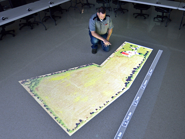Asmark's KJ Johnson studies a field map projected on the floor. Students learn strategies for approaching each field. (DTN/Progressive Farmer photo by Jim Patrico)