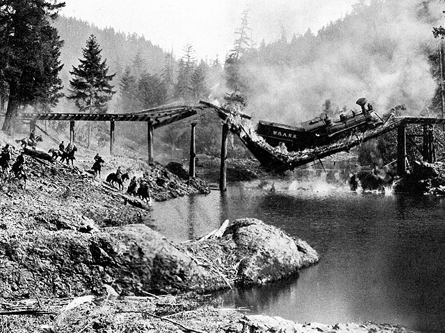 "The longer the great locomotive of trade remains stopped in the middle of a critical bridge, the greater the chance of a catastrophe. (Train wreck scene from the 1926 Buster Keaton movie ""The General."" Photo courtesy of the Dorena Historical Society)"