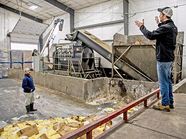 "Brett Reinford (right) talks with worker Dennis Walton in the ""depackaging"" building, where food waste is separated from its packaging and blended in the anaerobic digester with the manure.(Progressive Farmer photo by Tom Gralish)"