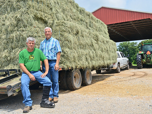 By the time hay seasons ends, Scott Woolfolk (left) and dad, Johnny, will have handled more than 25,000 small, 50-pound hay bales, selling most into the area's horse market.