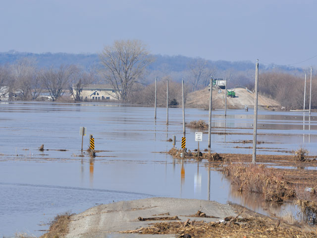 A road is washed out and a bridge that normally goes over Interstate 29 is now a storage spot for equipment above the water. At least 40 miles of Interstate 29 in Iowa are underwater. (DTN photo by Chris Clayton)