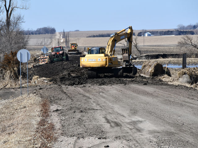 Construction equipment sits on a road being repaired over the Logan Creek just north of Uehling, Nebraska. Many rural roads and state highways in the state were damaged from floods that hit the area last week. (DTN photo by Russ Quinn)