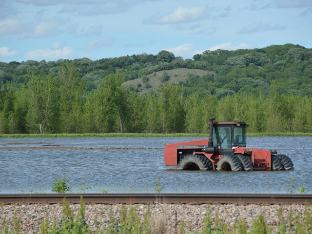 A tractor remains flooded along the Missouri River just north of Hamburg, Iowa. The town has been battling floods for more than two months and water began rising again last week on the river, halting some recovery efforts. (DTN photo by Chris Clayton)
