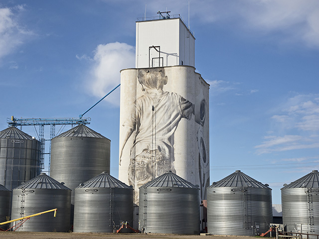 A 110-foot grain elevator at Faulkton, South Dakota, provides a canvas where artist Guido Van Helten paints details like a wrinkle in jeans and even highlights in strands of hair, Image by Greg Lamp