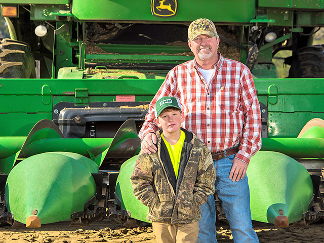 Dan Gause (with son Daniel) gives precision farming the credit for boosting his whole-farm dryland corn averages by 60 bushels to the acre, Image by Fred Salley