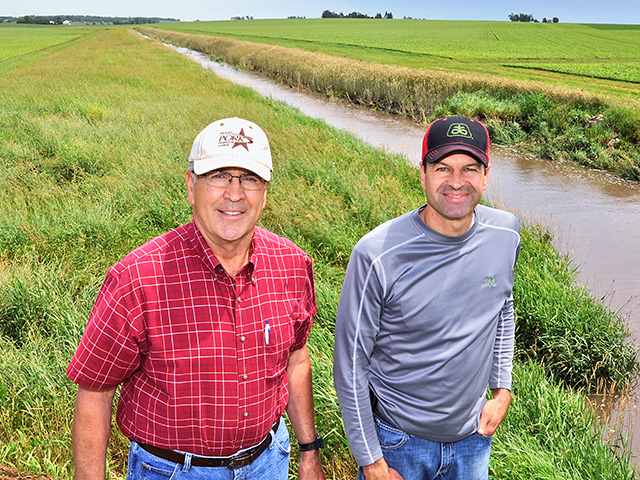 John (left) and son Brian Weber added a water-control structure and tile to establish a saturated buffer to reduce nitrates entering the creek from field tile, Image by Lynn Betts