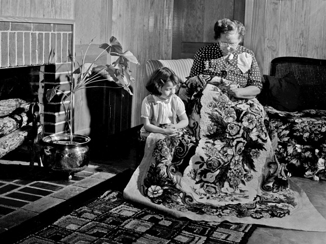 Grandmother making a rug with her grandchild looking on in Mt. Hope, AL, in 1953. (Progressive Farmer image by Jack Goodson)
