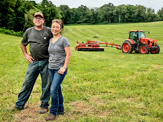Kenny and Natsuko Merrick stand in front of their original hay meadow. They have restored the soils with no-till and cover crops. (DTN/Progressive Farmer photo by Jodi Miller)