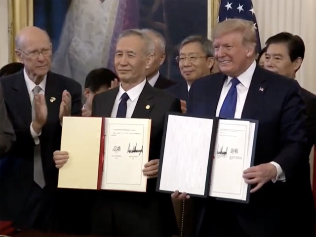 With Sen. Pat Roberts, R-Kan., looing on from the left, President Donald Trump signs the phase one trade agreement on Wednesday with China's Vice Premier Liu He. The president's trade team said China will buy $40 billion in agricultural products from the U.S. each of the next two years. (Photo shot from White House live feed)
