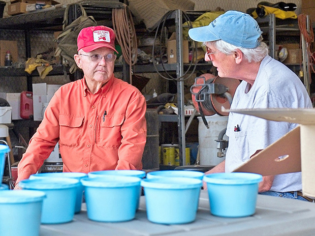 Farmer Gary Frost (left) and nematode developer Elson Shields talk as nematodes wait in their containers before the inoculation. (Progressive Farmer image by Patrick Porter, Texas A&M)