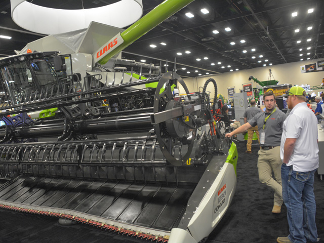 A CLAAS representative talks to a farmer about the capabilities of its new Lexion 7500 combine at Commodity Classic in San Antonio last month. (DTN photo by Matthew Wilde)