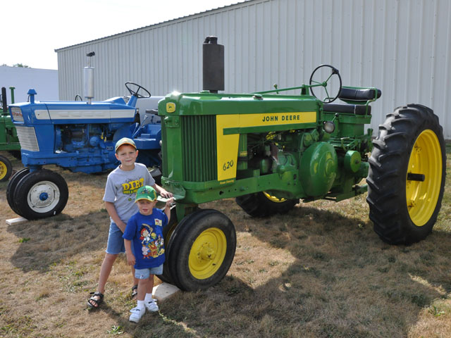 """Kyle and Burke Quinn stand in from their great-grandpa's 1957 John Deere 620 tractor in 2012. While the tractor remains the same today, the boys are six years older and considerably taller. Photo by Russ Quinn.�"